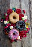 Grupo malsano pero delicioso de tortas dulces del buñuelo del azúcar y porciones de caramelos gomosos en la tabla de madera del v fotografía de archivo