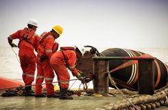 Grupo marinho que faz a operação da conexão da mangueira fotografia de stock royalty free