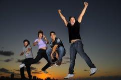 Grupo masculino joven feliz que salta al aire libre Imagenes de archivo