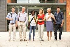 Grupo mezclado de estudiantes fuera de la universidad fotos de archivo