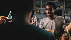 Grupo mezclado de la pertenencia étnica de amigos jovenes felices que comen la pizza y que tienen bebidas en un partido de casa c almacen de video