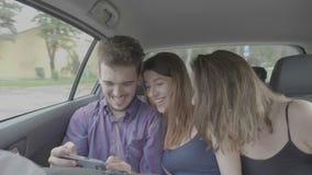 Grupo milenario de amigos locos que toman el vídeo del bumerán del selfie dentro de un coche mientras que ellos que van en viaje almacen de video