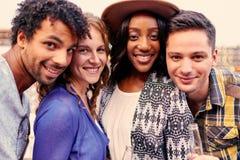 grupo millenial Multi-étnico de amigos que toman una foto del selfie con el teléfono móvil en terrasse del tejado en la puesta de Foto de archivo