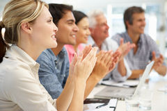Grupo misturado que aplaude na reunião de negócio