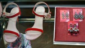 Grupo moderno de acessórios vermelhos do ` s das mulheres - sandálias e brincos na exposição da janela fotografia de stock