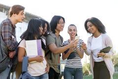 Grupo multiétnico de estudiantes felices jovenes que usan el teléfono móvil Imagenes de archivo