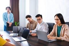 grupo multiétnico de socios comerciales que trabajan en la tabla con los ordenadores portátiles en moderno fotos de archivo