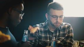 Grupo multi-étnico de amigos que comem a pizza e que têm bebidas em uma festa em casa Os jovens apreciam o alimento na mesa de co vídeos de arquivo
