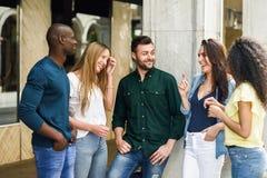 grupo Multi-étnico de amigos que se divierten junto en fondo urbano fotos de archivo libres de regalías