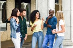 grupo Multi-étnico de amigos que se divierten junto en fondo urbano fotos de archivo