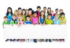 Grupo Multi-étnico de crianças que guardam o quadro de avisos vazio foto de stock royalty free
