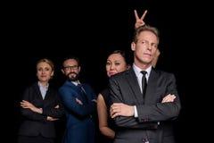 Grupo multi-étnico de empresários maduros que estão com braços cruzados e de gracejo isolado no preto fotos de stock