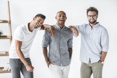 grupo multi-étnico de estar de sorriso novo dos homens de negócios imagem de stock royalty free