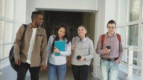 grupo Multi-étnico de estudiantes que caminan abajo del pasillo espacioso blanco de la universidad y que hablan feliz después de  almacen de video