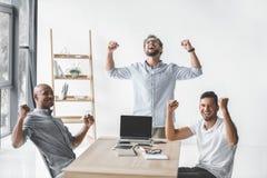 grupo multi-étnico de executivos novos que comemoram o sucesso no local de trabalho imagens de stock