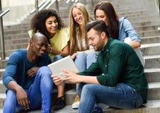grupo Multi-étnico de gente joven que mira una tableta imagen de archivo