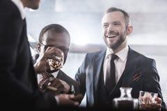 Grupo multi-étnico de homens de negócios que passam o tempo que bebe junto o uísque e o fumo fotografia de stock royalty free