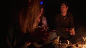 Grupo multi-étnico de jovens que sentam-se pela fogueira tarde em músicas da noite e do canto e o jogo da guitarra cheerful vídeos de arquivo