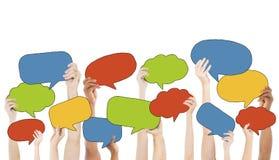 Grupo Multi-étnico de manos que llevan a cabo burbujas del discurso Imagenes de archivo