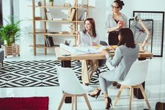 Grupo multi-étnico de mulheres de negócios novas que trabalham com modelos e que discutem foto de stock royalty free