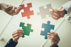 grupo Multi-étnico de profissional do negócio que põe o enigma quatro imagens de stock
