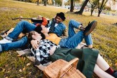 grupo multicultural de amigos que descansan sobre la manta junto foto de archivo libre de regalías