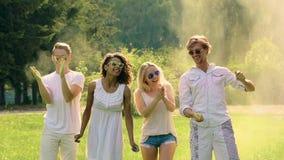 Grupo multicultural de amigos que lanzan el polvo colorido sobre las cabezas en el festival metrajes