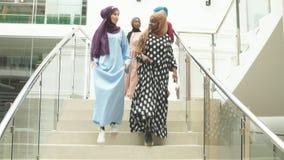 Grupo multicultural de estudiantes árabes femeninos que van abajo de las escaleras de la universidad almacen de metraje de vídeo
