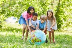 Grupo multicultural de globo del mundo de los rollos de los niños imagen de archivo libre de regalías