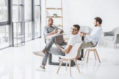 grupo multicultural de hombres de negocios que se sientan en el lugar de trabajo en luz foto de archivo