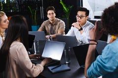 grupo multicultural de socios comerciales que tienen discusión en la tabla con los ordenadores portátiles en moderno imagenes de archivo