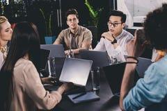 grupo multicultural de socios comerciales que tienen discusión en la tabla con los ordenadores portátiles en moderno fotografía de archivo libre de regalías