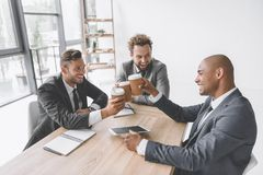 grupo multicultural de xícaras de café descartáveis de sorriso do tinido dos homens de negócios imagem de stock