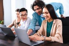grupo multicultural sonriente de colegas del negocio que tienen reunión en la tabla con los ordenadores portátiles en moderno foto de archivo libre de regalías