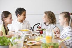 Grupo multicultural sonriente de niños que comen la comida imágenes de archivo libres de regalías