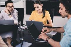 grupo multicultural sonriente de socio comercial que habla en la tabla con los ordenadores portátiles en moderno imagen de archivo libre de regalías