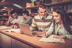Grupo multinacional de estudantes alegres que estudam na biblioteca da universidade fotografia de stock