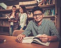 Grupo multinacional de estudiantes alegres que estudian en la biblioteca de universidad foto de archivo libre de regalías