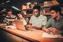 Grupo multinacional de estudiantes que estudian en la biblioteca de universidad fotos de archivo