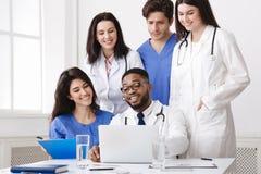 Grupo multinacional de los doctores Looking In Laptop fotografía de archivo