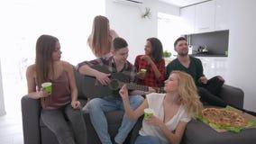 Grupo multirracial de amigos que bailan y que cantan la sentada en el sofá en un apartamento moderno grande mientras que el much almacen de metraje de vídeo
