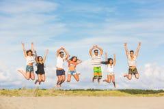 Grupo multirracial de amigos que saltan en la playa imagenes de archivo