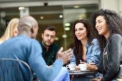 Grupo multirracial de cinco amigos que comen un café junto imagenes de archivo