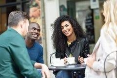 Grupo multirracial de cuatro amigos que comen un café junto imágenes de archivo libres de regalías