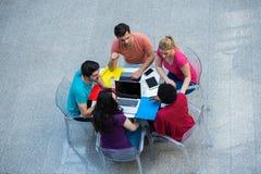 Grupo multirracial de estudiantes jovenes que estudian junto Tiro de alto ángulo de la gente joven que se sienta en la tabla fotografía de archivo libre de regalías