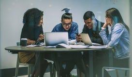 Grupo multirracial de estudiantes jovenes que usan los teléfonos imágenes de archivo libres de regalías