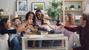Grupo multirracial de gente joven que celebra en casa con la pizza y el alcohol almacen de video