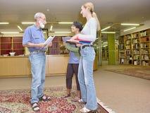 Grupo multirracial de gente amistosa que charla en biblioteca Fotografía de archivo
