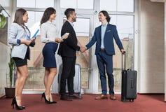 Grupo na entrada, dois homem de negócios Meeting Handshake de Meeting Business People do recepcionista do hotel Imagens de Stock