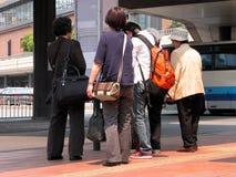 Grupo na estação de autocarro fotografia de stock